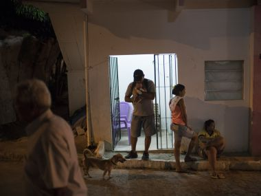 Daniele Ferreira dos Santos (center right) stands outside her house as her ex-husband holds their son Juan Pedro, who was born with microcephaly, outside her house in Recife, Pernambuco state, Brazil. AP