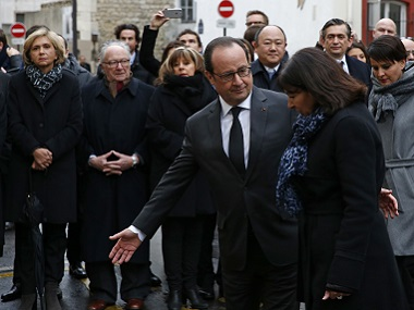 French President Francois Hollande (C) and Paris Mayor Anne Hidalgo arrive to unveil a commemorative plaque outside the former offices of French weekly satirical newspaper Charlie Hebdo. AFP