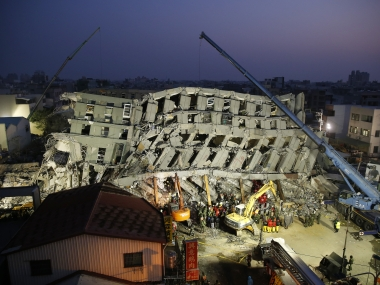 Emergency rescuers search for the missing in a collapsed building from the earthquake. AP