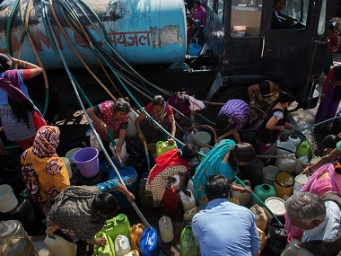 Residents of the eastern New Delhi neighborhood of Sanjay Camp use hoses to fill water jugs from a water distribution truck.  AFP