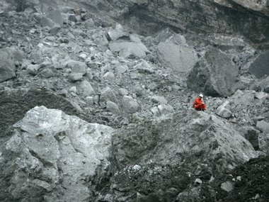 A rescuer takes a break as he searches for survivors at a landslide site in the Jiwei Mountain area of Wulong county, Chongqing municipality, June 6, 2009. At least 80 people were feared buried in the landslide at a southwestern Chinese iron ore mine, state media said.  REUTERS/Stringer (CHINA DISASTER IMAGES OF THE DAY) CHINA OUT. NO COMMERCIAL OR EDITORIAL SALES IN CHINA