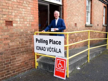 Irish Minister for Jobs, Enterprise and Innovation, and Fine Gael member Richard Bruton, poses for pictures outside a polling station in Dublin, Ireland, on February 26, 2016, during a general election. Ireland voted on Friday in an election which could make it the latest eurozone country to face political instability as anger over austerity erodes support for traditional parties. / AFP / LEON NEAL
