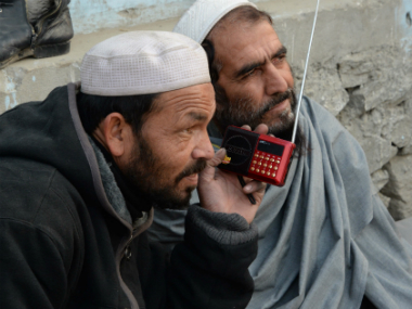 In a file photo, Afghan men listen to a radio broadcast run by the Islamic State group in Jalalabad. AFP