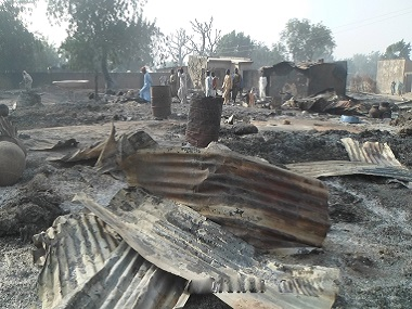 People walk past burnt out houses following an attack by Boko Haram in Dalori village. AP