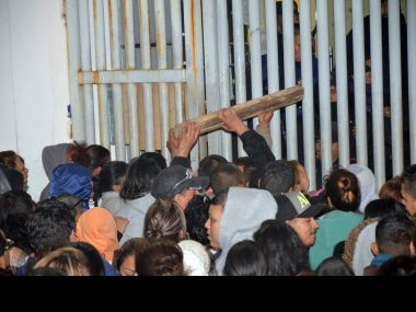 Relatives of inmates try to ram a piece of wood at police, who are standing on the other side of a gate, at the Topo Chico where a riot broke out around midnight, in Monterrey, Mexico. AP