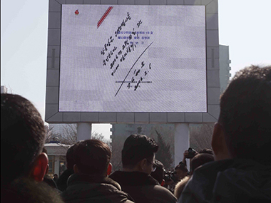 North Koreans watch a signed document b Kim Jong Un about the launch. AP