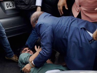BJP MLA OP Sharma assaulting CPI-M activist in Patiala House Court Complex on Monday. PTI