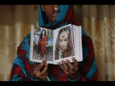 REMOVES REFERENCE TO SIDRA BEING AT WORK WHEN ATTACK TOOK PLACE - In this photo taken on Jan. 27, 2016, Sidra Kamwal shows pictures of herself before she was disfigured in an acid attack in Karachi, Pakistan. She had left her abusive husband and moved back in with her mother when another man proposed to her. The man refused to take no for an answer. He pestered her and harassed her. And then one day he told her that if couldn't have her, no one could, and threw acid in her face.(AP Photo/Shakil Adil)