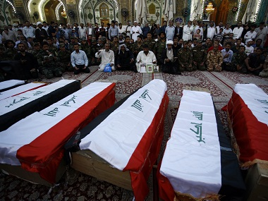 Iraqi civilians and soldiers mourn next to coffins containing the remains of ten of their comrades who were killed in the Speicher massacre. File photo AFP