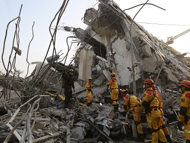 Rescue personnel work at the site where a 17-storey apartment building collapsed, after an earthquake in Tainan, southern Taiwan. Reuters