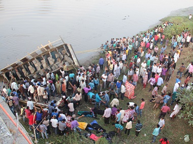 Rescue workers and villagers try to extract the injured and dead passengers from a Gujarat State Road Transport Corporation's passenger bus which plunged in to river Purna near Navsari, some 315 kms from Ahmedabad on Friday. AFP
