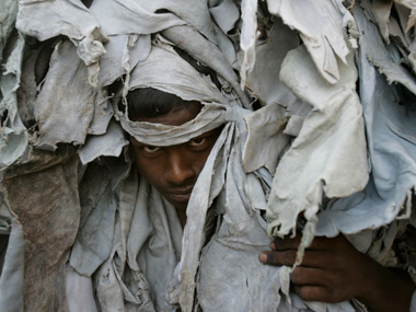 A labourer carries scrap leather from a traditional tannery in the eastern Indian city of Kolkata May 24, 2008. The traditional tannery uses dead animal skin from buffaloes and cows mostly, later treating it with chemicals to make leather goods, while the ones from buffaloes are used in machinery. Most of Kolkata's traditional tanneries are situated in the heart of the city, but they are being asked to relocate due to environmental concerns. REUTERS/Parth Sanyal (INDIA) - RTX64AB