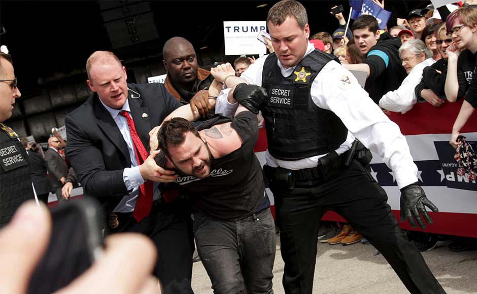 U.S. Secret Service agents detain a man after a disturbance as U.S. Republican presidential candidate Donald Trump spoke at Dayton International Airport in Dayton, Ohio March 12, 2016. REUTERS