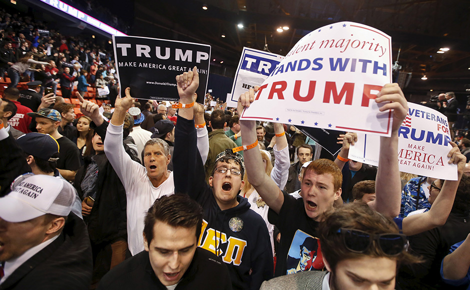 Trump supporters hold signs after Republican U.S. presidential candidate Donald Trump cancelled his rally at the University of Illinois at Chicago March 11, 2016. REUTERS