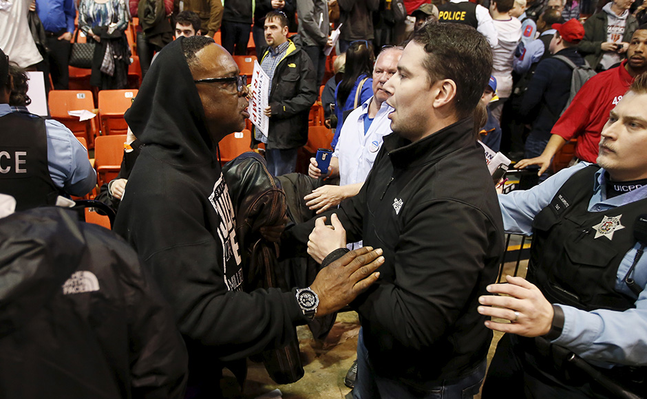 A Trump supporter (R) talks to a demonstrator (L) after Republican U.S. presidential candidate Donald Trump cancelled his rally at the University of Illinois at Chicago March 11, 2016. REUTERS