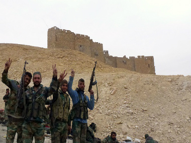 Syrian pro-governement forces gesture next to the Palmyra citadel on March 26, 2016, during a military operation to retake the ancient city from the jihadist Islamic State (IS) group. Getty Images