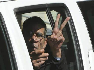 EgyptAir plane hijacking suspect Seif Eddin Mustafa flashes the victory sign as he leaves a court in a police car after a remand hearing as authorities investigate him on charges including hijacking, illegal possession of explosives and abduction in the Cypriot coastal town of Larnaca Wednesday, March 30, 2016. AP