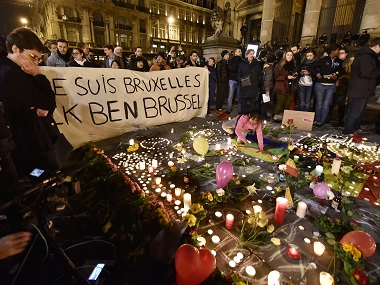 "People holding a banner reading ""I am Brussels"" behind flowers and candles to mourn for the victims. AP"