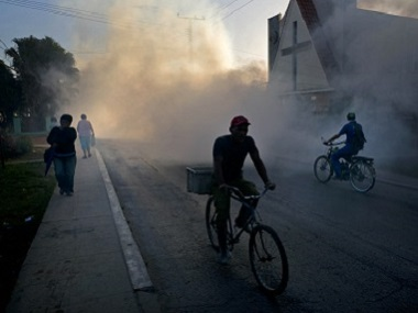 People make their way through fumigation fog, sprayed to kill Aedes Aegypti mosquitos, in Pinar del Rio, Cuba. AP