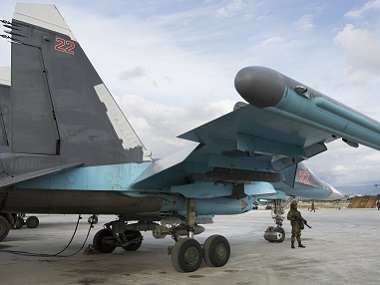 A Russian soldier stands guard next to a Su-34 bomber at Hemeimeem air base in Syria. AP