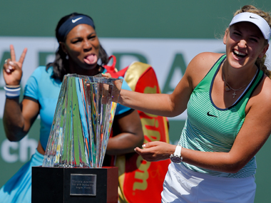 Runner up Serena Williams jokes as winner  Victoria Azarenka poses with the Indian Wells trophy. AP
