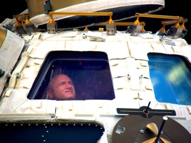 Astronaut Scott Kelly looks out the cupola of the International Space Station. NASA via AP