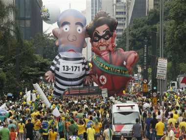 """Demonstrators parade large inflatable dolls depicting Brazil's former President Luiz Inacio Lula da Silva in prison garb and current President Dilma Rousseff dressed as a thief, with a presidential sash that reads """"Impeachment,"""" in Sao Paulo, Brazil, Sunday, March 13, 2016. AP"""