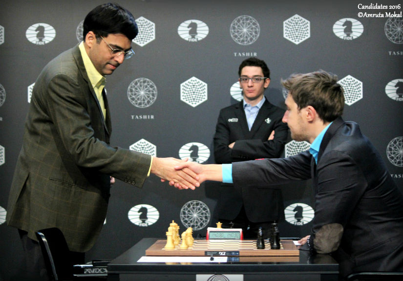 Viswanathan Anand (left) shakes hands with Sergey Karjakin before the start of the game at Moscow's Central Telegraph Building as Fabiano Caruana looks on. Amruta Mokal
