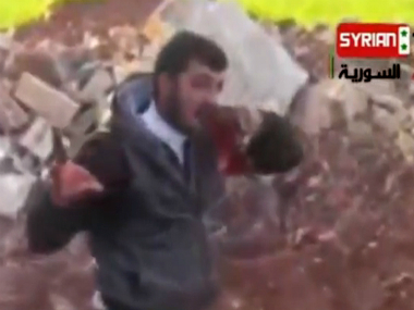 An image grab taken on May 15, 2013 from an undated video uploaded on YouTube allegedly shows Khaled al-Hamad, a rebel fighter known as Abu Sakkar and commander of the Omar al-Faruq brigade in Homs, Syria, holding the heart (L) and the liver (R) of a Syrian government soldier after cutting it out from his dead body. AFP