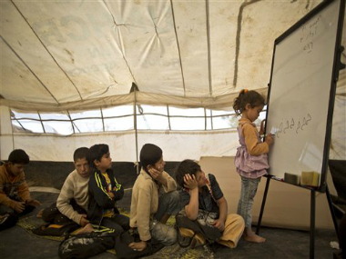 Syrian refugee Ghufran Ahmad, 5, writes on a board while she and other children attend a class at a makeshift school set up in a tent at an informal tented settlement in the Jordan Valley, Jordan, Thursday, March 31, 2016. AP