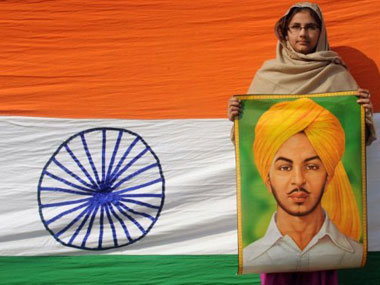A woman holds the painting of freedom fighter Bhagat Singh. AFP