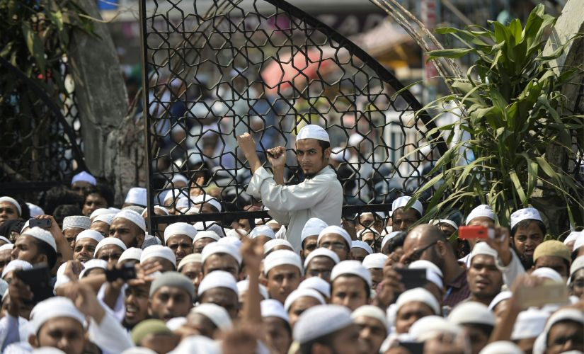 "Bangladeshi hardline Islamists protest outside the national mosque Baitul Mukarram in Dhaka on March 25, 2016. Thousands of Bangladeshi hardline Islamists have rallied across the country against an ""infidels'-initiated"" move to scrap Islam as the state-religion in the Muslim-majority nation. Nearly seven thousand activists of hardline group Hefazat-e-Islam carried banners and festoons and chanted slogans on Dhaka high roads after the Friday prayer booing the government for not taking ""sufficient actions"" to stop ""mockery"" against Islam, religion of nearly 90 percent of the population of the country. / AFP PHOTO / MUNIR UZ ZAMAN"