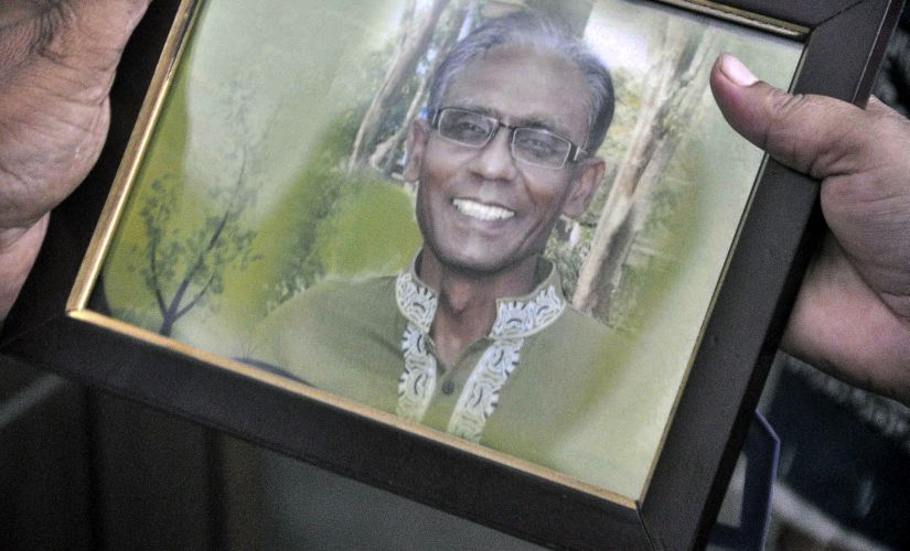 A man holds a portrait of Bangladeshi professor Rezaul Karim Siddique. AFP