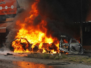 Flames engulf the wreckage of a car following a bomb explosion in southern Lebanese port city of Sidon on Tuesday. AFP