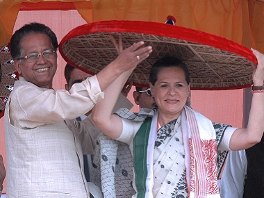 Congress Party President, Sonia Gandhi tries on a traditional Assamese hat assisted by Tarun Gigoi, Chief Minister of Assam during a rally in Tezpur. AFP