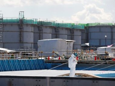 A worker, wearing protective suits and masks, takes notes in front of storage tanks for radioactive water at the tsunami-crippled Fukushima Dai-ichi nuclear power plant, operated by Tokyo Electric Power Co. (TEPCO), in Okuma, Fukushima Prefecture, northeastern Japan. To dump or not to dump a little-discussed substance is the question brewing in Japan as it grapples with the aftermath of the nuclear catastrophe in Fukushima five years ago. The substance is tritium. AP