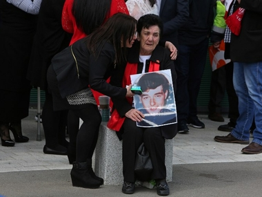 A woman holds an image of a victim of the 1989 Hillsborough disaster, as she reacts following the conclusion of the inquest into the disaster. AFP