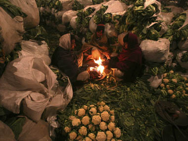 Vendors warm themselves by a fire amid stacked cauliflowers at Azadpur wholesale fruit and vegetable market in New Delhi January 14, 2012. The overall inflation situation will be manageable if the declining trend in food inflation continues for the next 3 months, Finance Minister Pranab Mukherjee said on Thursday. REUTERS/Parivartan Sharma (INDIA - Tags: ENVIRONMENT BUSINESS FOOD TPX IMAGES OF THE DAY)