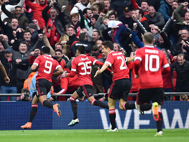 Manchester United players celebrate with the crowd after their late winner against Everton. AFP