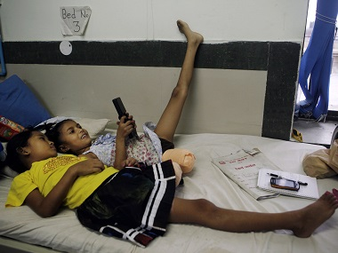 File photo of Khendo Tamang, left, and Nirmala Pariyar playing on a mobile phone at the Bir Trauma Center in Kathmandu. AP
