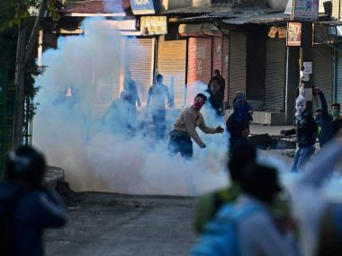 Angry youths throw stones on police during clashes which erupted after the killing of two youth allegedly in Army on Tuesday. PTI