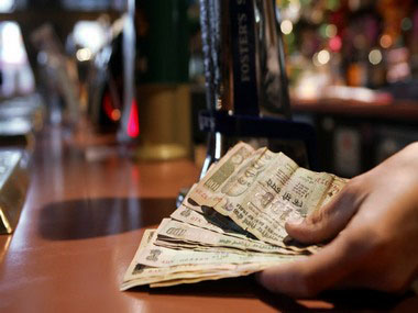 TO GO WITH AFP STORY BY KATHERINE HADDON A barman holds a handful of Indian rupees in a pub in Southall in west London on November 28, 2008. AFP PHOTO/Leon Neal