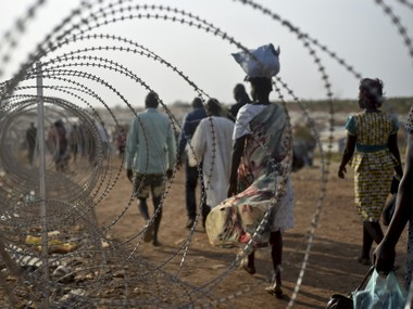 File image of displaced people walking next to a razor wire fence at the United Nations base in the capital Juba, South Sudan. AP