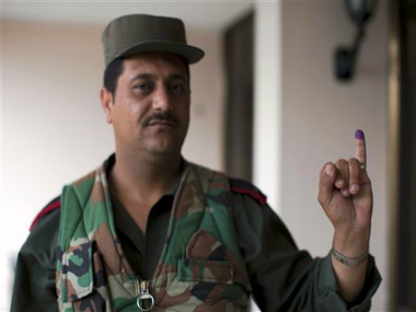 A Syrian policeman poses for a photograph showing his inked finger after voting outside a polling station during the parliamentary election in Damascus, Syria, Wednesday. AP