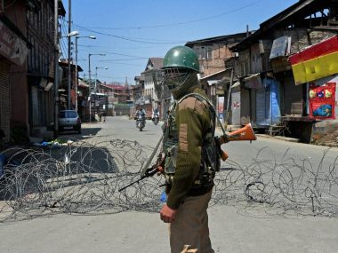 A security jawan stands guard at a street during the second day of strike following the killing of four civilians allegedly in Army and police firing, in Srinagar on Thursday. PTI