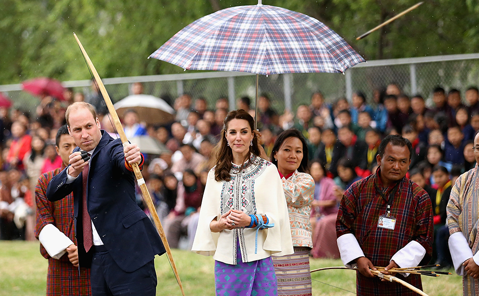 Prince William, Duke of Cambridge fires an arrow as Catherine, Duchess of Cambridge looks on during an Bhutanese archery demonstration on the first day of a two day visit to Bhutan on the 14th April 2016 in Paro, Bhutan. The Royal couple are visiting Bhutan as part of a week long visit to India and Bhutan that has taken in cities such as Mumbai, Delhi, Kaziranga, Bhutan and Agra. Getty