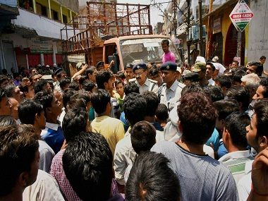 Police try to pacify local people protesting against the killing of Aditya Sachdeva. PTI.