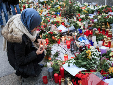 young Muslim woman lights a candle outside the French Embassy among candles, messages and flowers left by mourners commemorating the victims of the November attacks. Getty Images