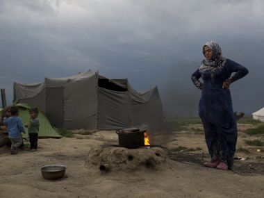 A Syrian woman cooks at the northern Greek border point of Idomeni, Greece. AP