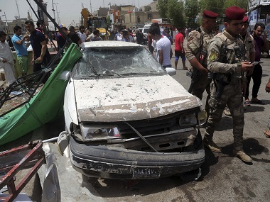 Security forces and citizens inspect the scene after a car bomb exploded at a crowded outdoor market in Baghdad's Sadr City. AP